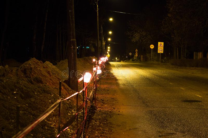 Allocation of the work site in the evening by lamps. Repair work along the road. Allocation of the work site in the evening by lamps stock photo