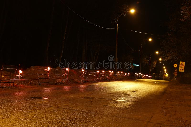 Allocation of the work site in the evening by lamps. Repair work along the road. Allocation of the work site in the evening by lamps stock image