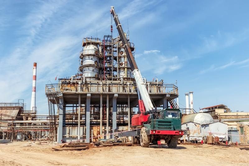 Repair work on the old oil and chemical production with the use of special heavy-duty truck crane. Repair work on the old oil and chemical production with the royalty free stock photos