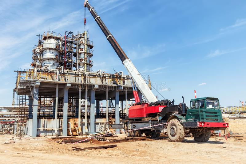 Repair work on the old oil and chemical production with the use of special heavy-duty truck crane. Repair work on the old oil and chemical production with the royalty free stock photo