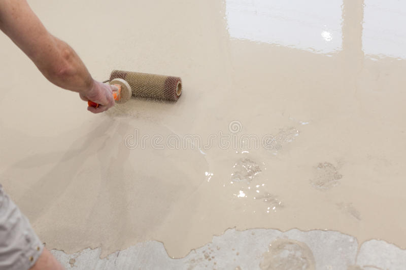 Repair work. Pouring floors in the room. Fill screed floor repair and furnish. Worker align cement with roller.  royalty free stock photography