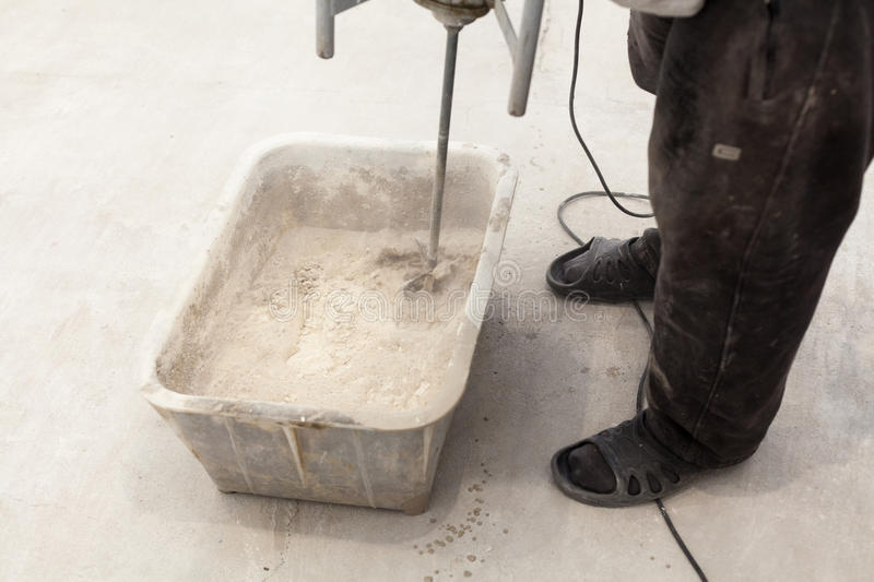 Repair work. Pouring floors in the room. Fill screed floor repair and furnish. Worker use concrete hand mixer to prepare cement.  stock images