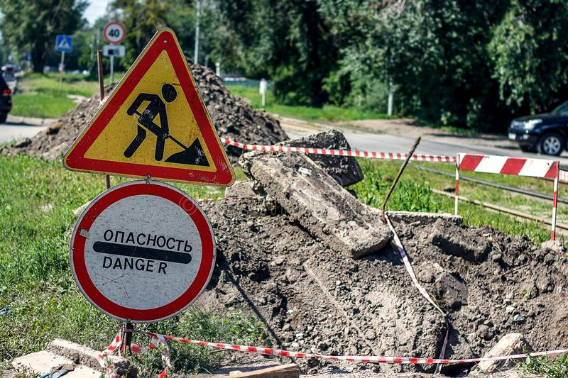 Road works on the city street. Road work and warning signs. Repair work. Road repair in city street. City street construction site with barricades, safety fence royalty free stock image
