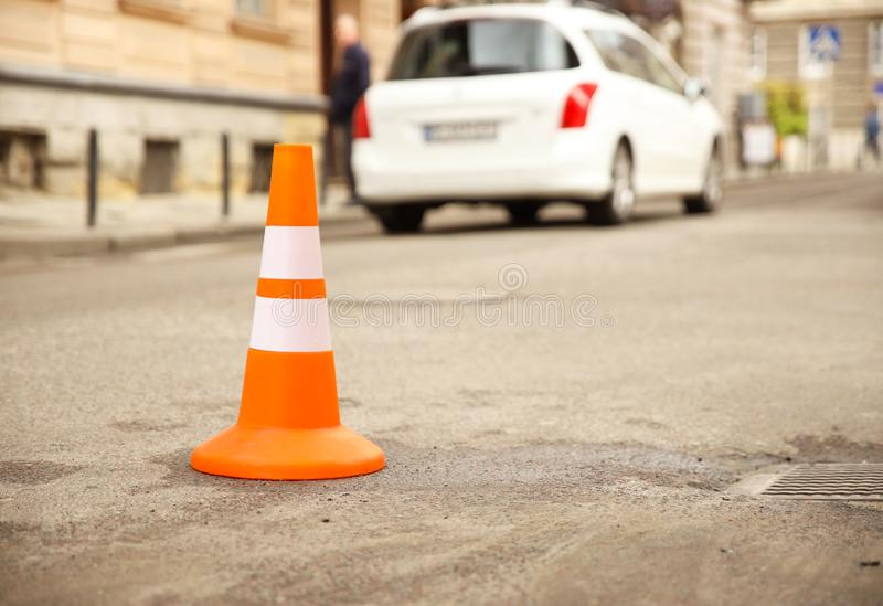 Repair work sign restricting traffic. White-orange plastic striped cone warning of danger. Tightening in traffic. Street of the stock images