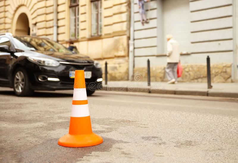 Repair work sign restricting traffic. White-orange plastic striped cone warning of danger. Tightening in traffic. Street of the royalty free stock photography