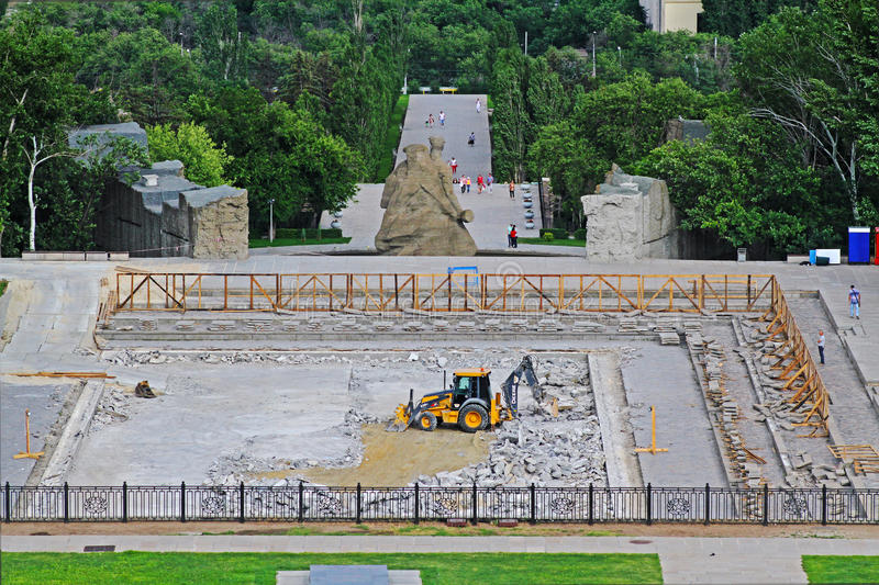 Repair works of the bottom of the `Lake of Tears` on Mamayev Kurgan with the help of a bulldozer with a pneumatic hammer and buc. Volgograd, Russia - June 24 royalty free stock image