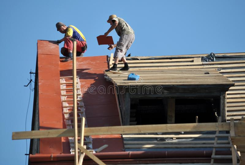 Repair works on replacement of metal roof tiles stock photography