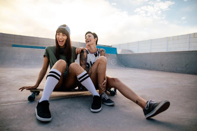 Repaire femelle d'amis de patineurs au parc de patin images stock