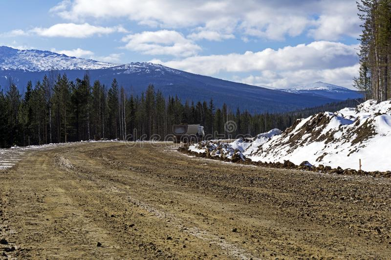 Dirt road with a dump truck in the northern highlands. Repaired dirt road with a dump truck in the northern mountainous woodland in winter royalty free stock images