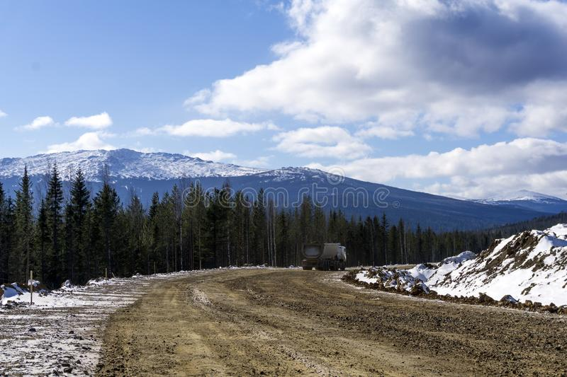 Dirt road with a dump truck in the northern highlands. Repaired dirt road with a dump truck in the northern mountainous woodland in winter stock photo