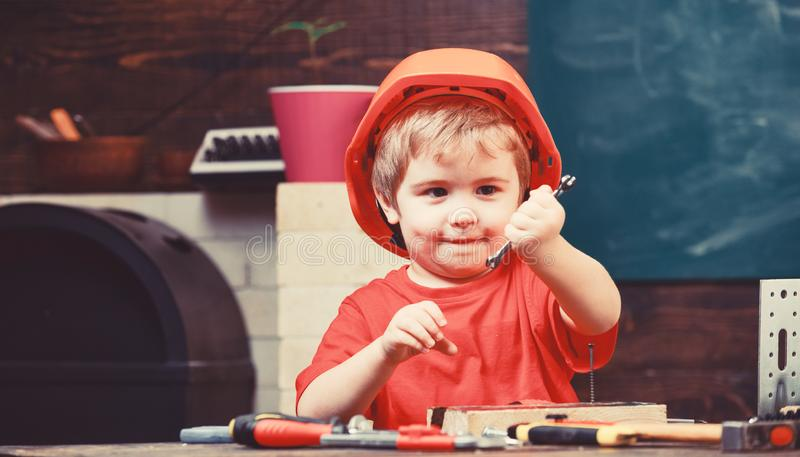 r Ребенок мечтая о будущей карьере в архитектуре или построении Мальчик ребенк в оранжевых трудной шляпе или шлеме стоковое изображение