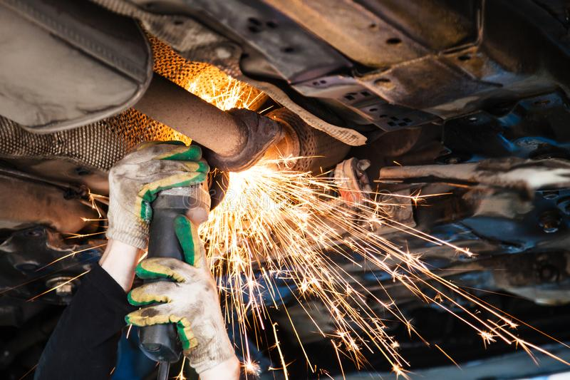Repairer cuts old silencer on car by angle grinder royalty free stock photos