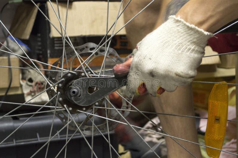 Repairerman repairing a bicycle wheel. In the workshop stock photos