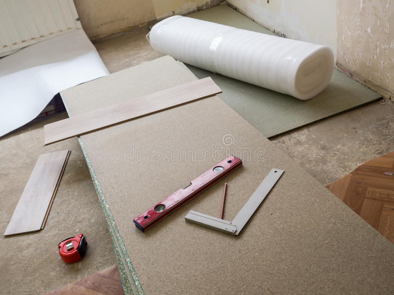 Repairing. Apartment& x27;s floor . Plates of pressed wood chips. Laminate. Measuring the Tools, building level, tape measure stock photos