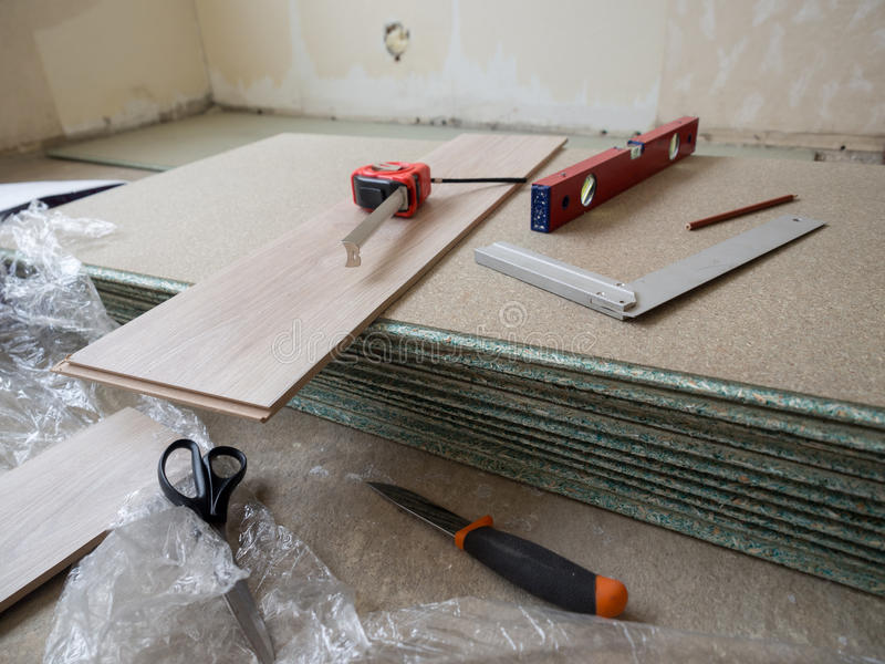 Repairing. Apartment& x27;s floor . Plates of pressed wood chips. Laminate. Measuring the Tools, building level, tape measure royalty free stock photography