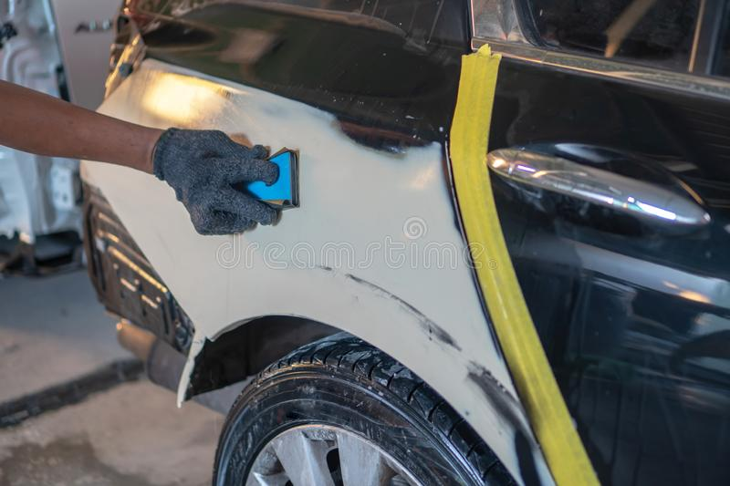 Car painting procedure at auto service store , Car accident at t. Repairing car body by puttying close up work after the accident by working sanding primer stock photography