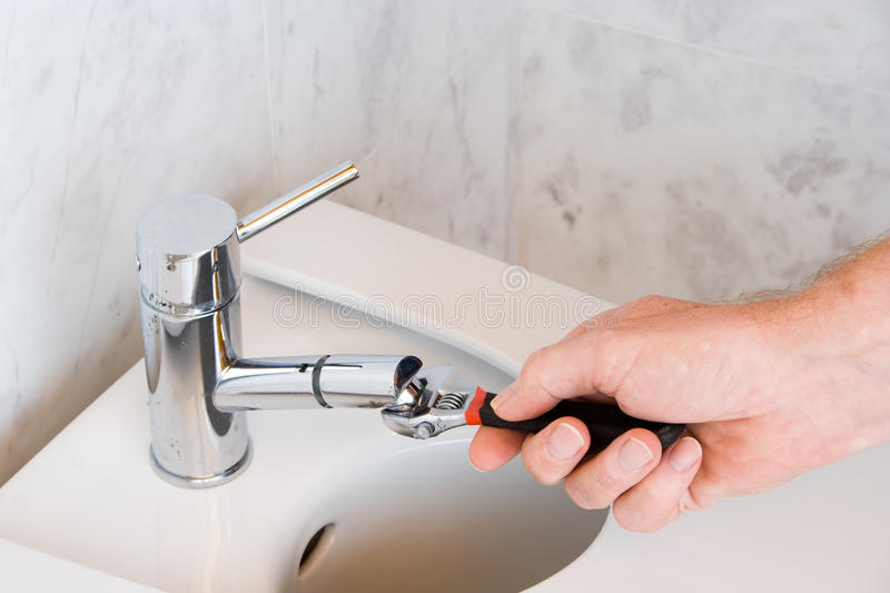 Repairing a faucet in a bathroom royalty free stock photography