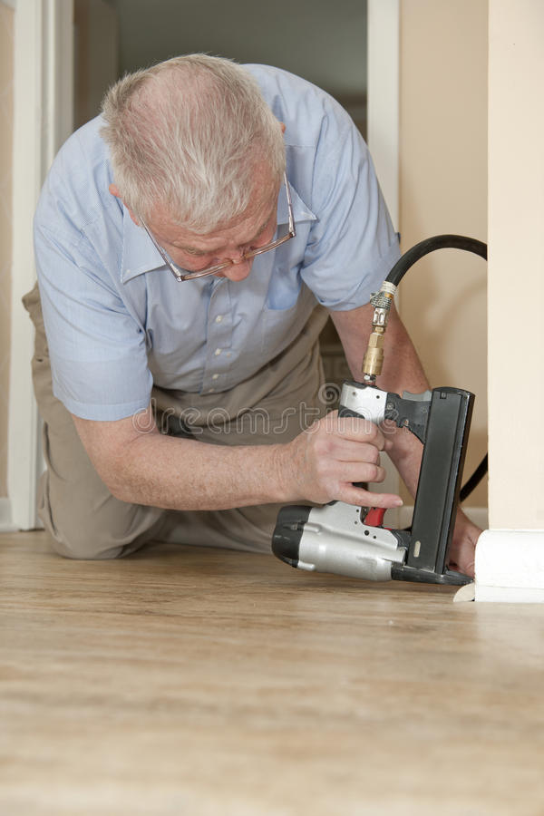 Repairing Home. A senior man on his hands and knees, using an air-compressed stapler to attach new quarter round to his baseboards. Space on bottom (home floor) stock images