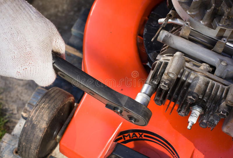 Repairing a lawn mower. Repairing lawn mower engine - motor royalty free stock photo