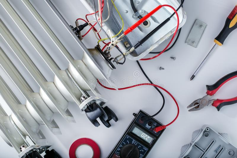 Repairing, measures electric heater. Concept repair electricity equipment. royalty free stock photos