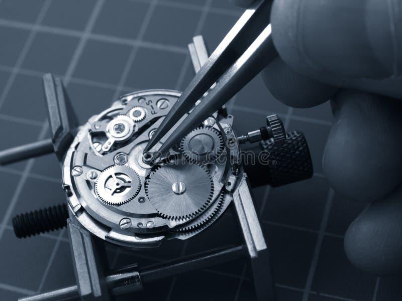 Repairing old watch. Watchmaker repairing old watch mechanism, taking small piece with tweezers stock photos