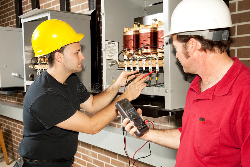 Repairing Power Distribution Center. Electricians working on an industrial power distribution center. Actual electricians and authentic accurate content stock photos