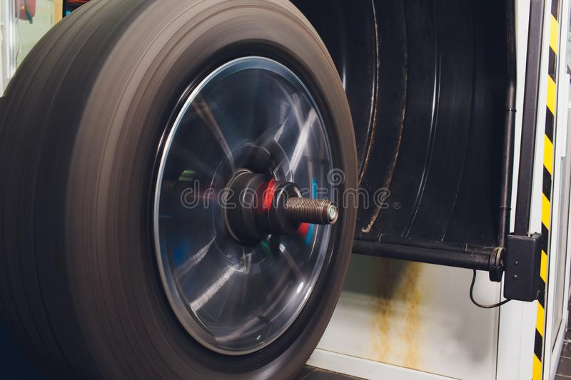 Repairman balances the wheel and installs the tubeless tire of the car on the balancer in the workshop. royalty free stock photos