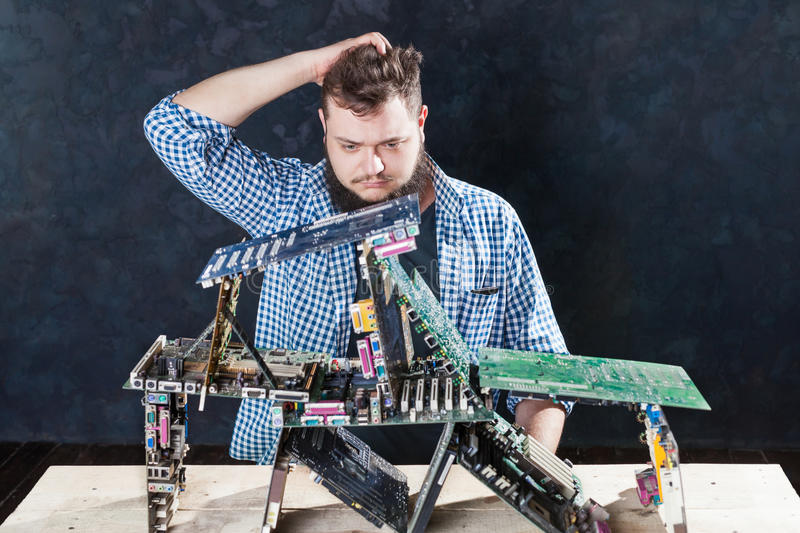 Repairman builds house of cards from motherboards stock photography