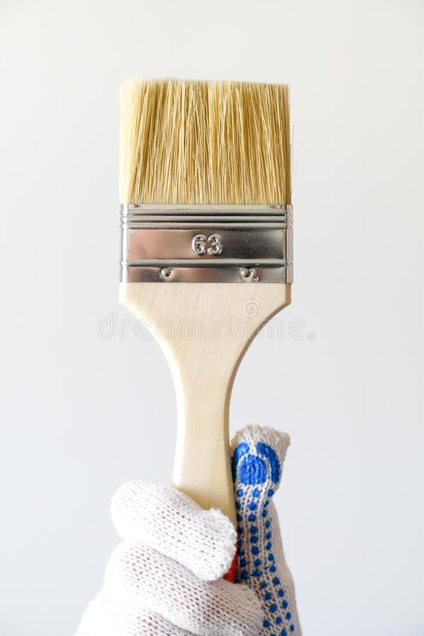 Repairman, carpenter, hired worker, girl or woman in protective gloves holding a new paint brush, on a white wall background. The royalty free stock photos