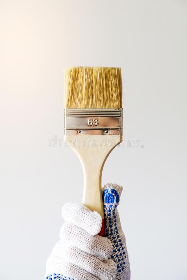 Repairman, carpenter, hired worker, girl or woman in protective gloves holding a new paint brush, on a white wall background. The. Concept of home and royalty free stock photos