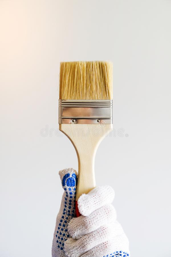 Repairman, carpenter, hired worker, girl or woman in protective gloves holding a new paint brush, on a white wall background. The royalty free stock images