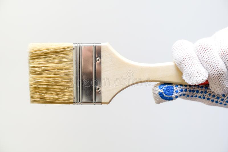 Repairman, carpenter, hired worker, girl or woman in protective gloves holding a new paint brush, on a white wall background. The stock photo