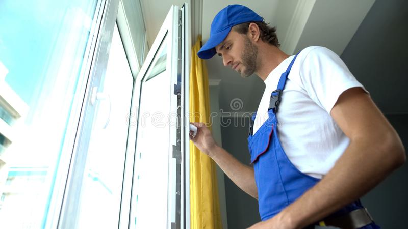 Repairman checking quality of window system installation, maintenance service royalty free stock image