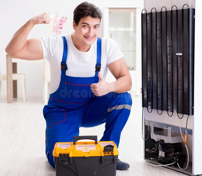 Repairman contractor repairing fridge in DIY concept. The repairman contractor repairing fridge in diy concept stock photography