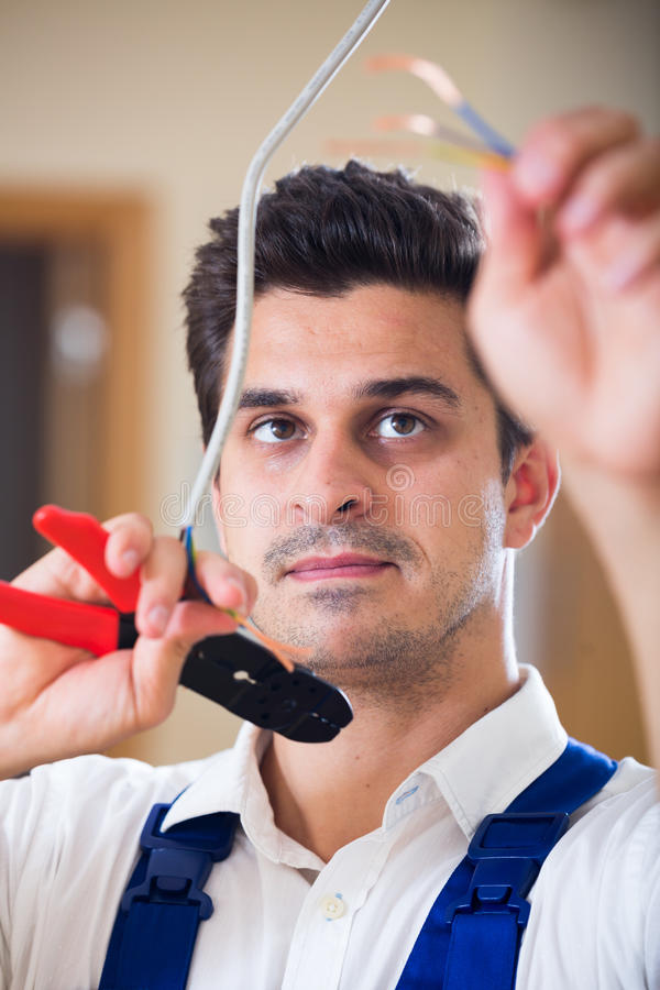 Repairman cutting wires with pliers in domestic interior royalty free stock image