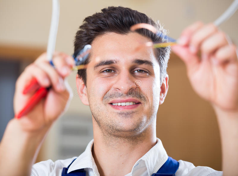 Repairman cutting wires with pliers in domestic interior stock photo