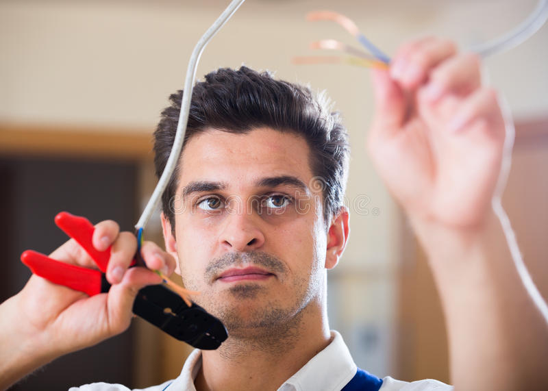 Repairman cutting wires with pliers in domestic interior royalty free stock photos