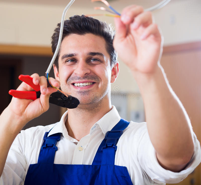 Repairman cutting wires with pliers in domestic interior royalty free stock photo