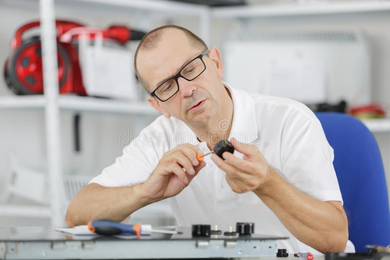 Repairman czyści elektroniczną część obrazy stock