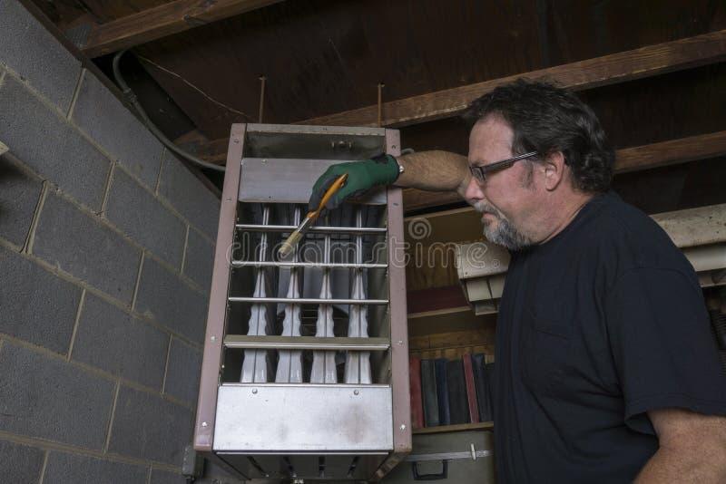Repairman Czyści kratownicy Benzynowy piec obrazy stock
