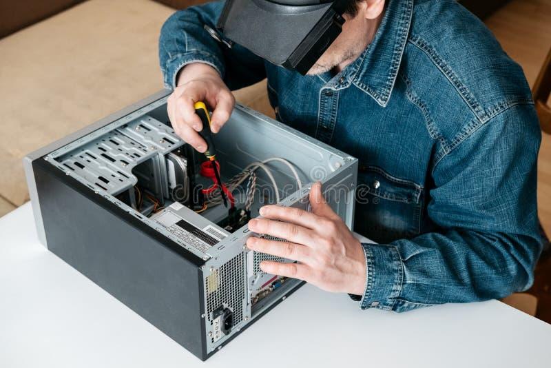 Repairman demontuje komputer osobistego Inżynier jest diagnostycznym i naprawianie łamającym komputerem osobistym w warsztacie El zdjęcia royalty free