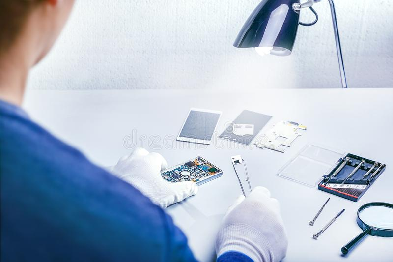 Repairman disassembling smartphone with tweezers. Repair smartphone, service center, technician, mobile phone, appliances, electro royalty free stock photo