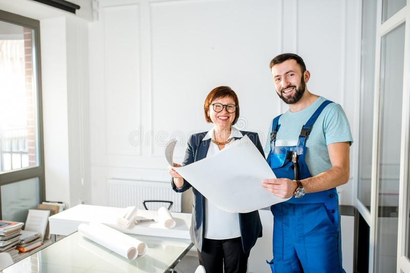 Repairman with senior architect or client at the office stock images