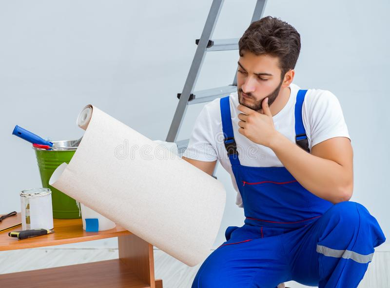Repairman doing renovation repair in the house with paper wallpa. Per stock photography