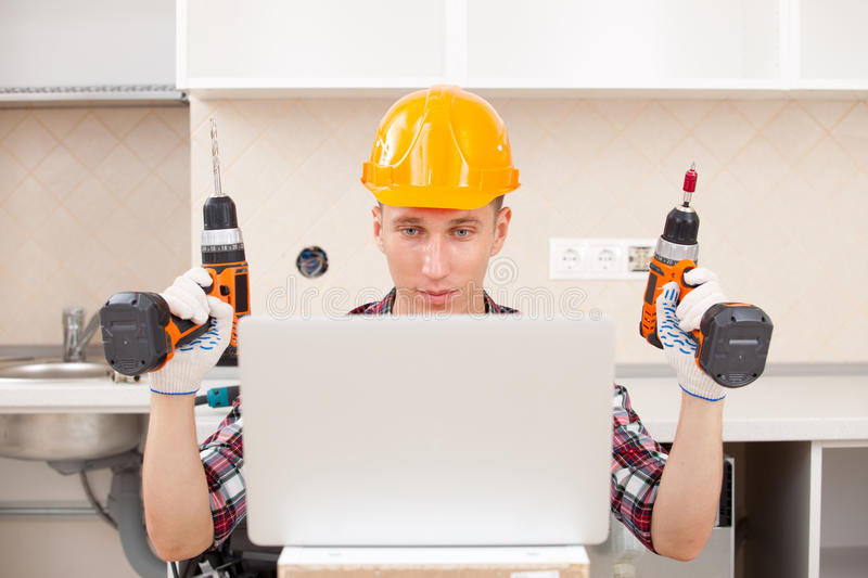 Repairman with a drill near a computer. Repairman with the screwdriver and drill near a computer stock photography
