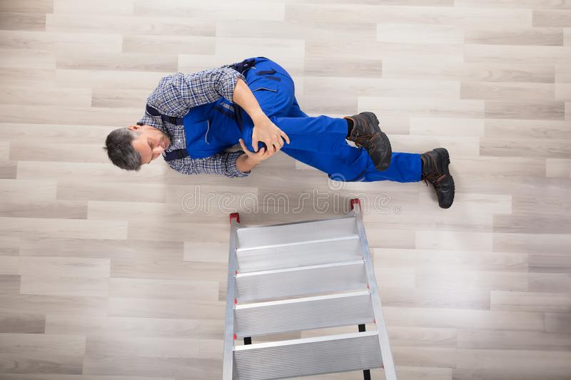 Repairman Fallen From Ladder. High Angle View Of A Repairman Fallen From Ladder On Hardwood Floor stock image