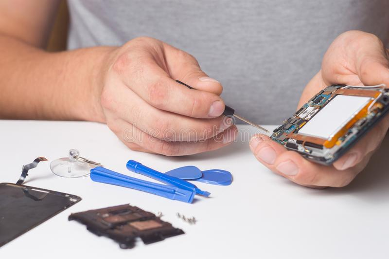 Repairman fixing disassembled smartphone with special tools and screwdrivers. concept of electronics repair devices royalty free stock images