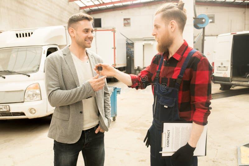 Repairman Giving Car Keys till kunden royaltyfri bild