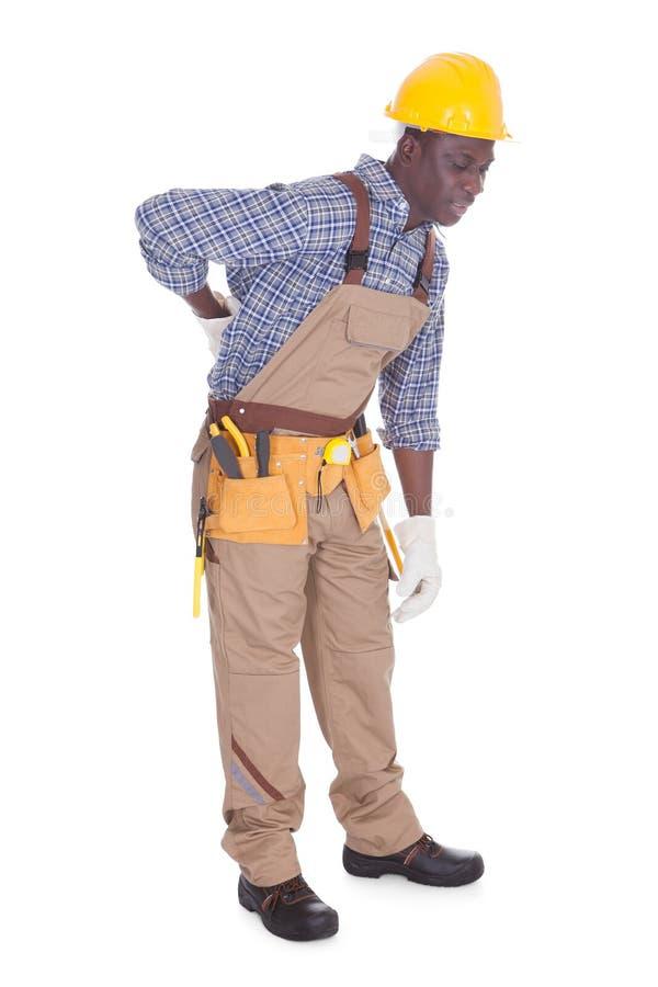 Repairman Having Back Ache. Young Repairman Having Back Ache Over White Background stock photo