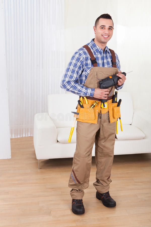 Repairman holding drill machine in living room royalty free stock images